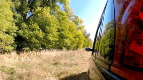 Car driving through the countryside. The camera is left outside. Beautiful reflection on the car body stock footage