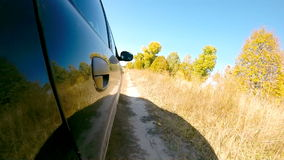 Car driving through the countryside. The camera is right outside. Beautiful reflection on the car body stock footage