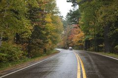 Car driving on a curving road in northern Minnesota with trees i royalty free stock photo