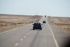 Car driving on desert road royalty free stock photo