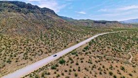 Car driving on a dirt road through dry Arizona desert stock footage