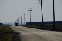 Car Driving Down Country Road Headlights Power Lines and Poles Stock Photo
