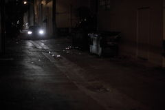 Car driving down a dark alley royalty free stock image