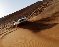 Car driving down sand dune stock photography