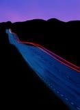 Car driving at dusk Stock Photo