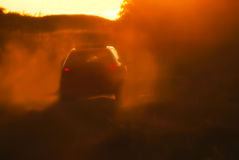 Car driving through dust in the sunset Stock Photo