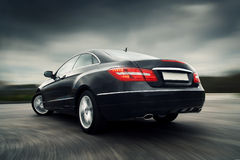 Car driving fast. Rear view of black luxury coupe driving fast royalty free stock images