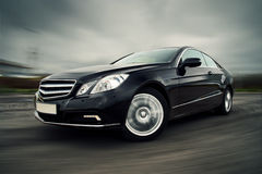 Car driving fast. Front view of black luxury coupe driving fast stock photo