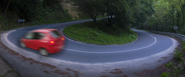 Car driving fast on a curved road Royalty Free Stock Photos