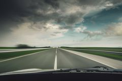 Car driving fast down on the highway before the rain Stock Image