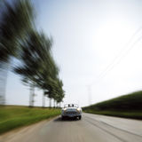 Car driving fast down road Stock Image