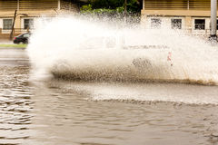Car driving fast through flood water on the road Royalty Free Stock Photography