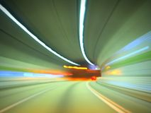 Fast speed car driving tunnel. Motion blurred picture of a fast car driving on a modern highway road inside a tunnel with neon lights of different colors. High