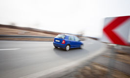 Car driving fast through a sharp turn. Traffic concept: car driving fast through a sharp turn (motion blur is used to convey movement Stock Photo