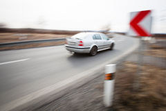 Car driving fast through a sharp turn. Traffic concept: car driving fast through a sharp turn (motion blur is used to convey movement Stock Image