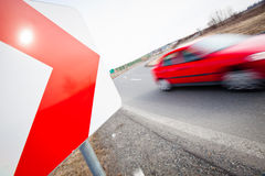 Car driving fast through a sharp turn. Traffic concept: car driving fast through a sharp turn (motion blur is used to convey movement Royalty Free Stock Images