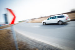 Car driving fast through a sharp turn. Traffic concept: car driving fast through a sharp turn (motion blur is used to convey movement Royalty Free Stock Photography