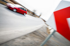Car driving fast through a sharp turn. Traffic concept: car driving fast through a sharp turn (motion blur is used to convey movement Royalty Free Stock Photo