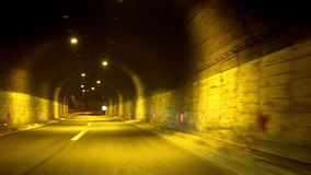 Car driving fast in tunnel at night stock footage