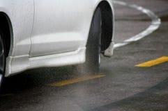 Car driving fast under the rain. White car detail driving fast under the rain Stock Photo