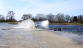 Car driving on the flood way, Lithuania. Black car driving on the flood road in spring in Silute region stock images