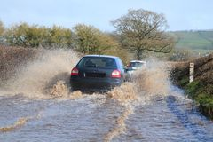 Car driving through a flooded road Stock Photo