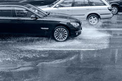 Car driving on flooded road with splashing water after heavy rai Royalty Free Stock Images