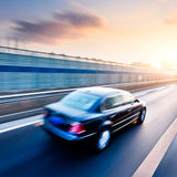 Car driving on freeway, motion blur. Car driving on freeway at sunset, motion blur Stock Images