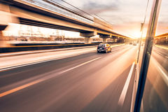 Car driving on freeway, motion blur. Car driving on freeway at sunset, motion blur Stock Photo