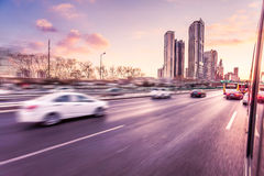 Car driving on freeway at sunset, motion blur Stock Image