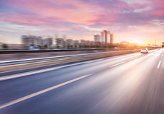 Car driving on freeway at sunset, motion blur stock photos