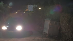 Car driving in the gloomy countryside at night. Car with headlamps on driving on the dark countryside road at night. Dismal place with trash container on the stock video