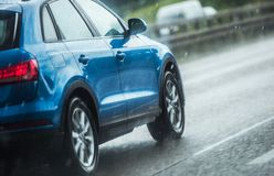 Car Driving in Heavy Rain. Blue Modern Vehicle on the Highway During Summer Storm with Heavy Rainfall royalty free stock photography