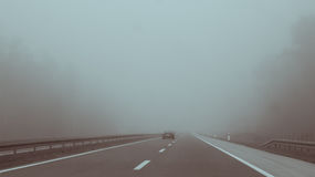 Car driving on highway entering fog Royalty Free Stock Image
