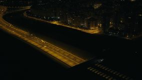 Car driving in highway tunnel with bright lighting on night street modern city. Drone view. Car traffic on highway road on background building and sports stock video footage