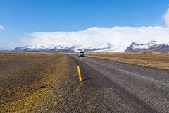 Car driving on the Icelandic ring road passes the Vatna Glacier. A car driving the ring road in South Iceland passes a tongue of the Vatna Glacier in South Royalty Free Stock Photo