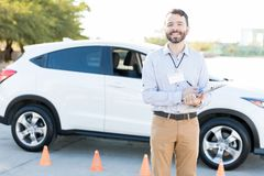 Car Driving Instructor Checking Checklist. Handsome Hispanic male teacher holding checklist for driving exam royalty free stock images