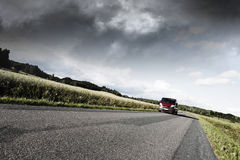 Car driving on lonely country road Stock Photography