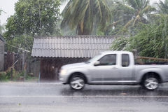 Car driving motion through gale rain on front wooden house. In rural road Royalty Free Stock Photography