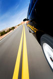 Car driving on mountain road. Low rear angle with natural motion blur Stock Photos