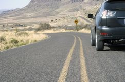 Car Driving in Mountains. Car suv driving on desert mountain road Stock Image