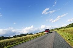 Car driving on a narrow country road. Car, suv, driving along on a lonely narrow country-road, summer, green fields and meadows. sweden Royalty Free Stock Image