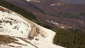 Car driving on narrow road in Beklemeto pass, Balkan mountains, Bulgaria. Melting snow in spring time, dangerous driving condition stock video footage