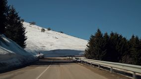 Car driving on narrow road in Beklemeto pass, Balkan mountains, Bulgaria. Melting snow in spring time, dangerous driving condition stock footage