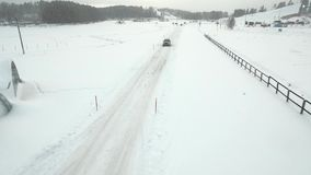 Car Driving Over Winter Road. Aerial view of a snowy forest with high pines and road with a car in the winter. Top view of winter road, trees and bushes covered stock video footage