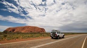 Car Driving Past Ayers Rock/Uluru Stock Photo