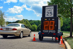 Car Driving by Police Speed Limit Monitor. Car driving too fast by a police speed limit monitor trailer in a residential neighborhood (property and driver Royalty Free Stock Photo