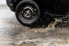 Car driving through a pothole with splashes of water stock photo