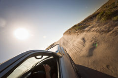 Car driving on a potholed dirt road. Under a searing sun across flat dry countryside Royalty Free Stock Image