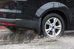 Car driving through a puddle on a flooded road with water and splashes caused by heavy rain. Royalty Free Stock Images